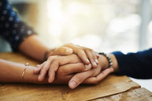 Two people holding hands in comfort at State Line Treatment Services: Addiction Treatment in Ohio